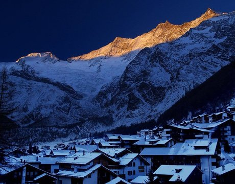 Chalets in Saas Fee - a view at night across the resort centre towards the glacial peaks